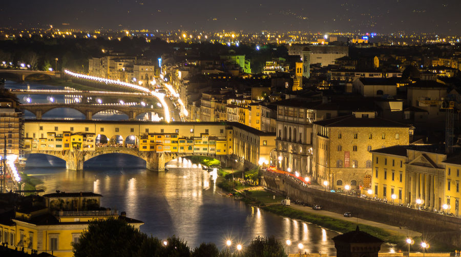Illuminated Ponte Vecchio Over Arno River At Night