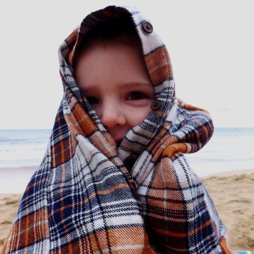 Portrait of child wrapped in blanket at beach against sky