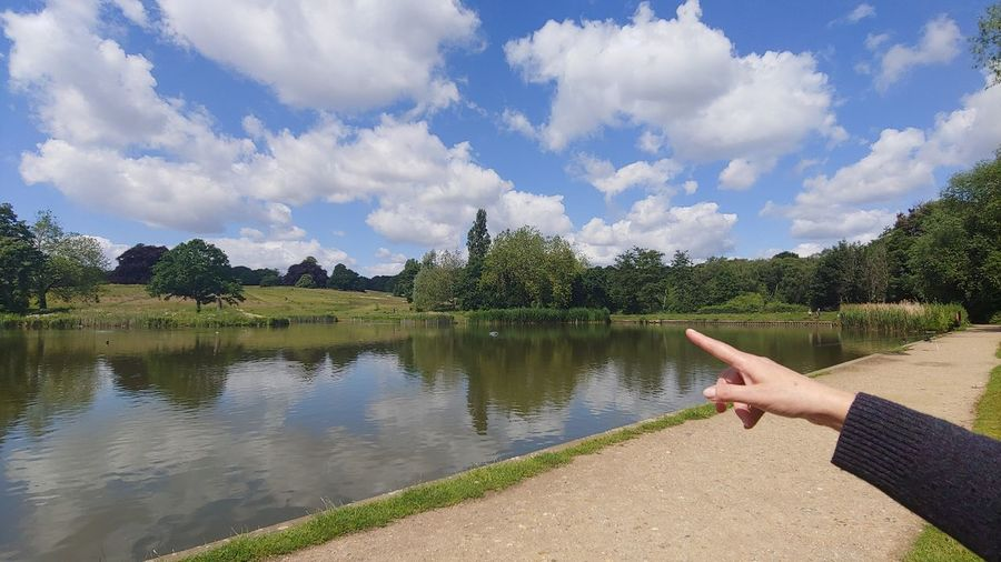 Close-up of person pointing against sky