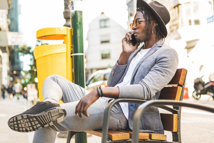 Man looking away while sitting on street in city