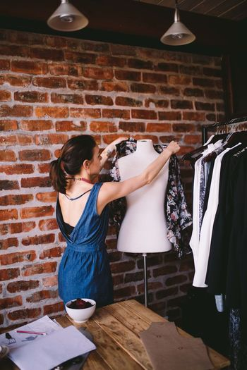 Female fashion designer arranging clothes on mannequin against brick wall