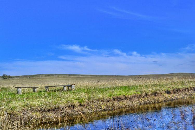 View of rural landscape against blue sky