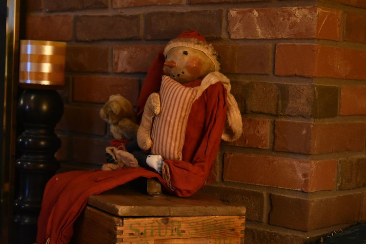Primitive Doll Christmas Santa, Pillow, Candle Wood Box, Old Red, Stripes Brick Wall Indoors, Fireplace Hearth Christmas Decoration , Hat Rosy Cheeks, Dark Eyes Sitting