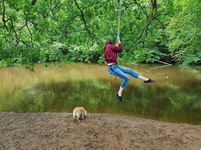 Young woman sitting on rope swing by pond