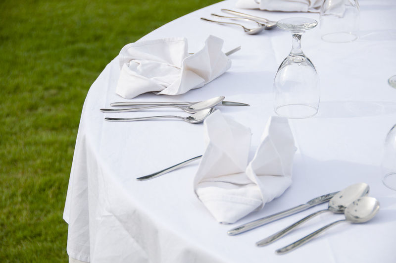 High angle view of cutlery and napkins on dining table at lawn