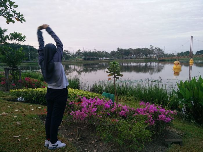Beauty In Nature Casual Clothing Day Flower Full Length Grass Growth Lake Leisure Activity Lifestyles Nature One Person Outdoors People Plant Real People Rear View Sky Standing Tree Water