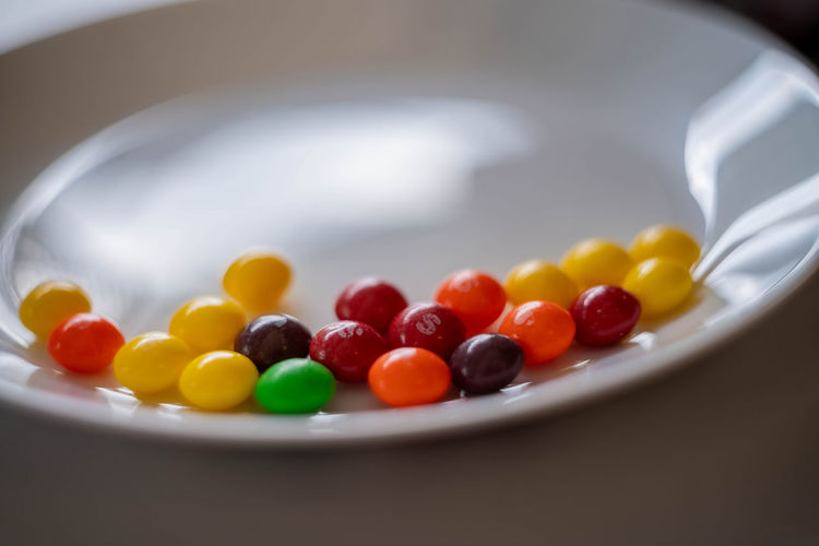 Close-up of multi colored candies in plate on table
