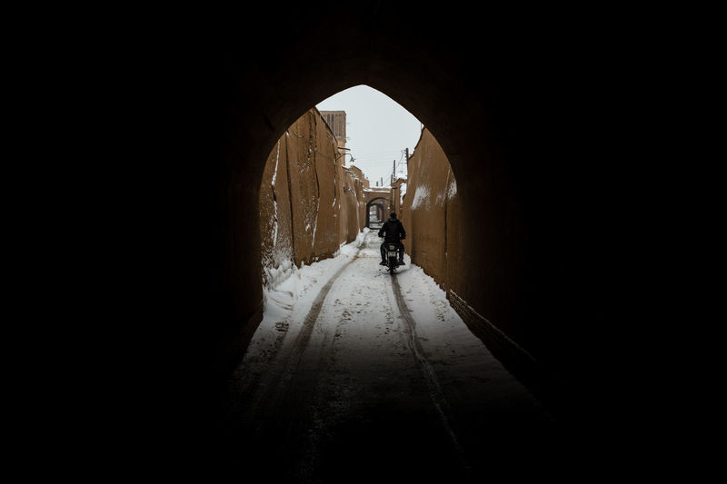 A lone male motorcycle rider travels along a snow covered narrow passage out of a dark tunnel in the back streets of Yazd, Iran. Cold Weather Motorcycle Arch Architecture Built Structure Cold Temperature Dark Day Direction Full Length Indoors  Lifestyles Light At The End Of The Tunnel Nature One Person Real People Rear View Snow Snowing The Way Forward Transportation Tunnel Walking Winter