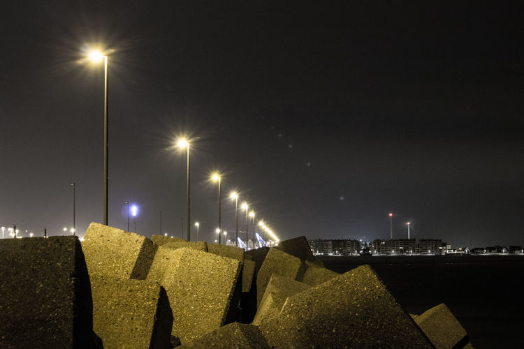 Low Angle View Of Illuminated Street Light On Shore At Night
