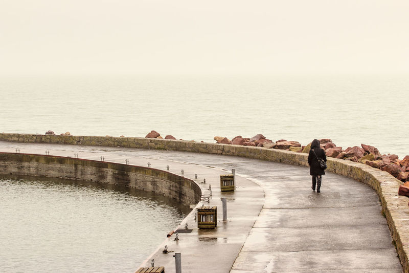 Rear View Of Woman Walking On Pier Over Lake