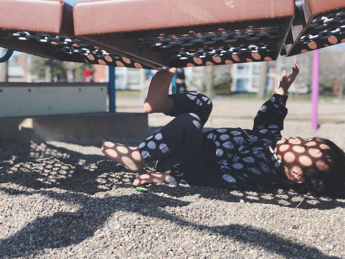 Boy Lying Below Play Equipment At Playground