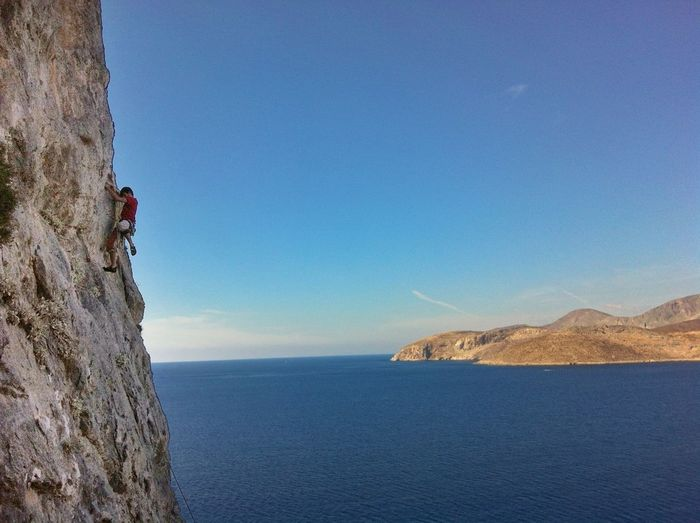 Man climbing rock against calm sea
