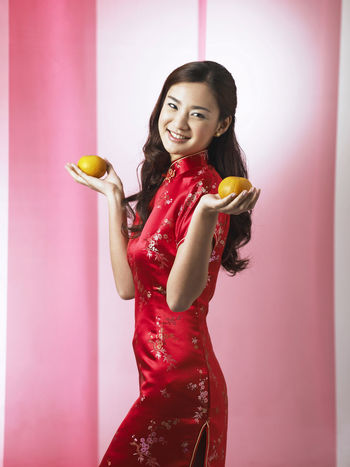 chinese woman holding pair of mandarin oranges greeting Gong Xi Fa Cai Greeting Happiness Mandarin Oranges Beautiful People Beautiful Woman Beauty Cheerful Cheongsam Chinese Ethnicity Chinese New Year Holding Indoors  Looking At Camera One Person Only Women Orange - Fruit Portrait Qipao Red Smile Smiling Studio Shot Young Adult Young Women