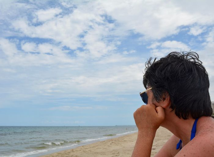 Side view of woman sitting on beach against cloudy sky
