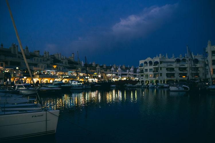 Sailboats moored in harbor against buildings at night