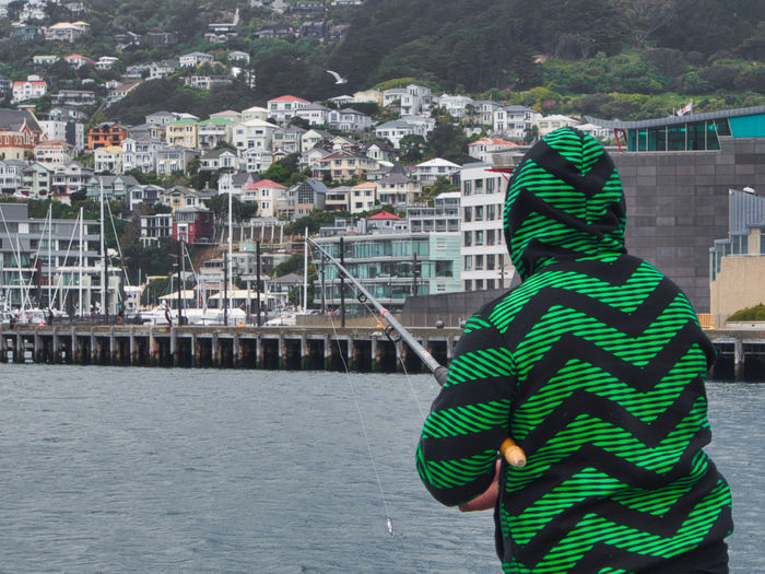 Fishing in style from the Wellington waterfront Fashion Stories Architecture Building Exterior Built Structure City Cityscape Day Lifestyles One Person Outdoors People Real People Rear View Water Fashion Stories An Eye For Travel #urbanana: The Urban Playground Moments Of Happiness