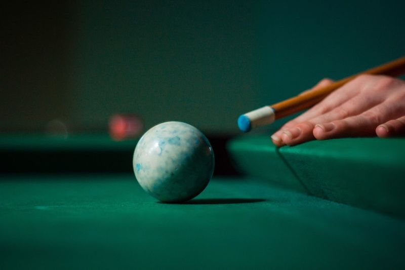 Cropped hand of person hitting pool ball with cue