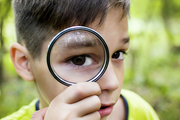 Close-up of boy looking through magnifying glass