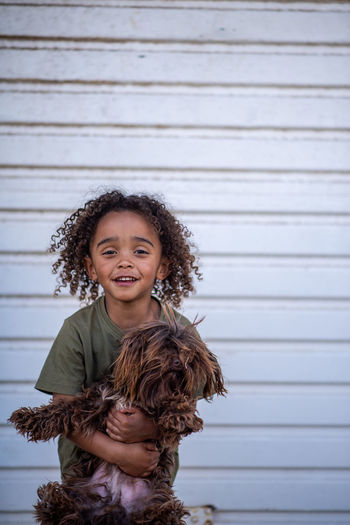 Smiling boy holding dog while standing against wall