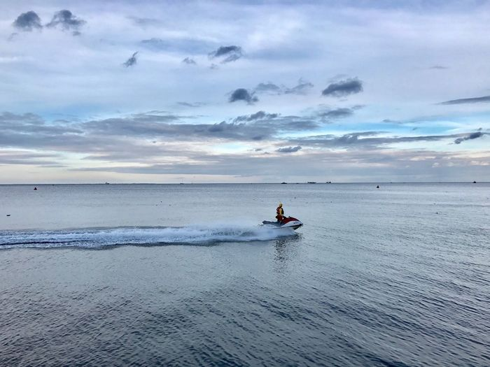 Person riding jet boat in sea against sky during sunset