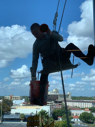 Low angle view of man working against sky in city