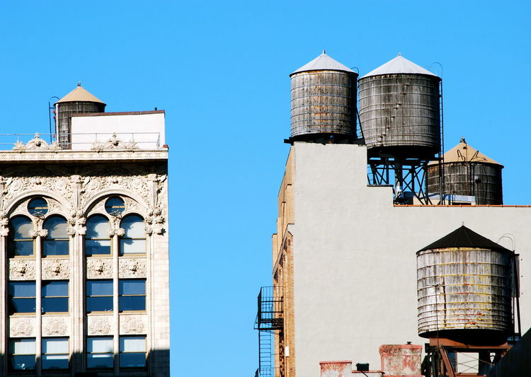 Low Angle View Of Water Tanks On Apartment Buildings Against Clear Sky