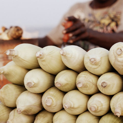 Midsection of man selling sweetcorns at market stall