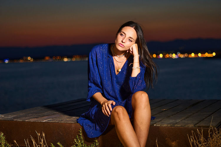 Beautiful young woman sitting against sky during sunset