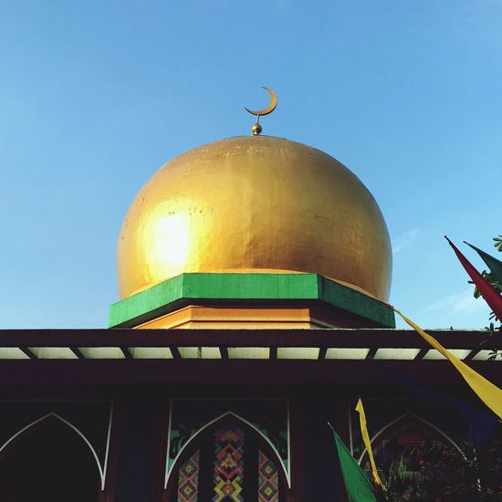Low angle view of golden mosque against clear blue sky