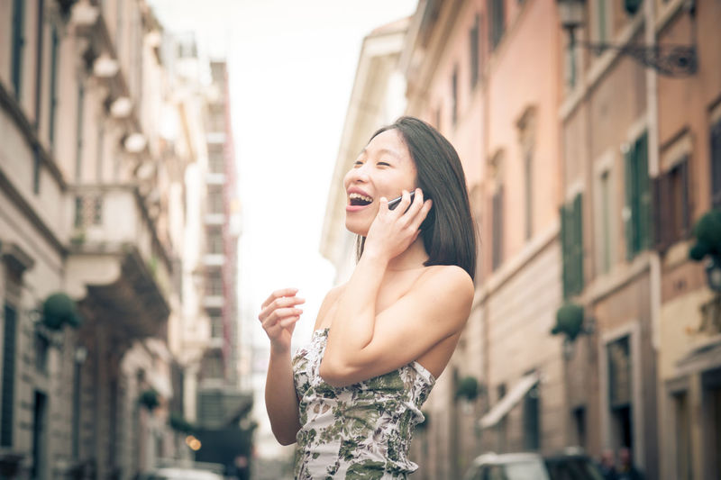 Smiling woman talking on mobile phone in city