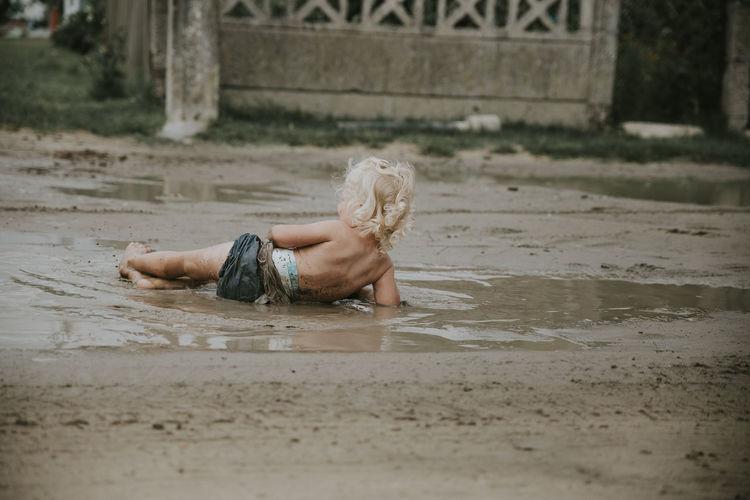 Full length of shirtless man lying in water