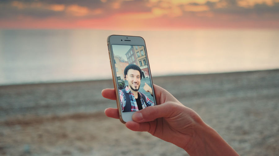 Cropped hand of woman holding mobile phone while video conferencing with man at beach