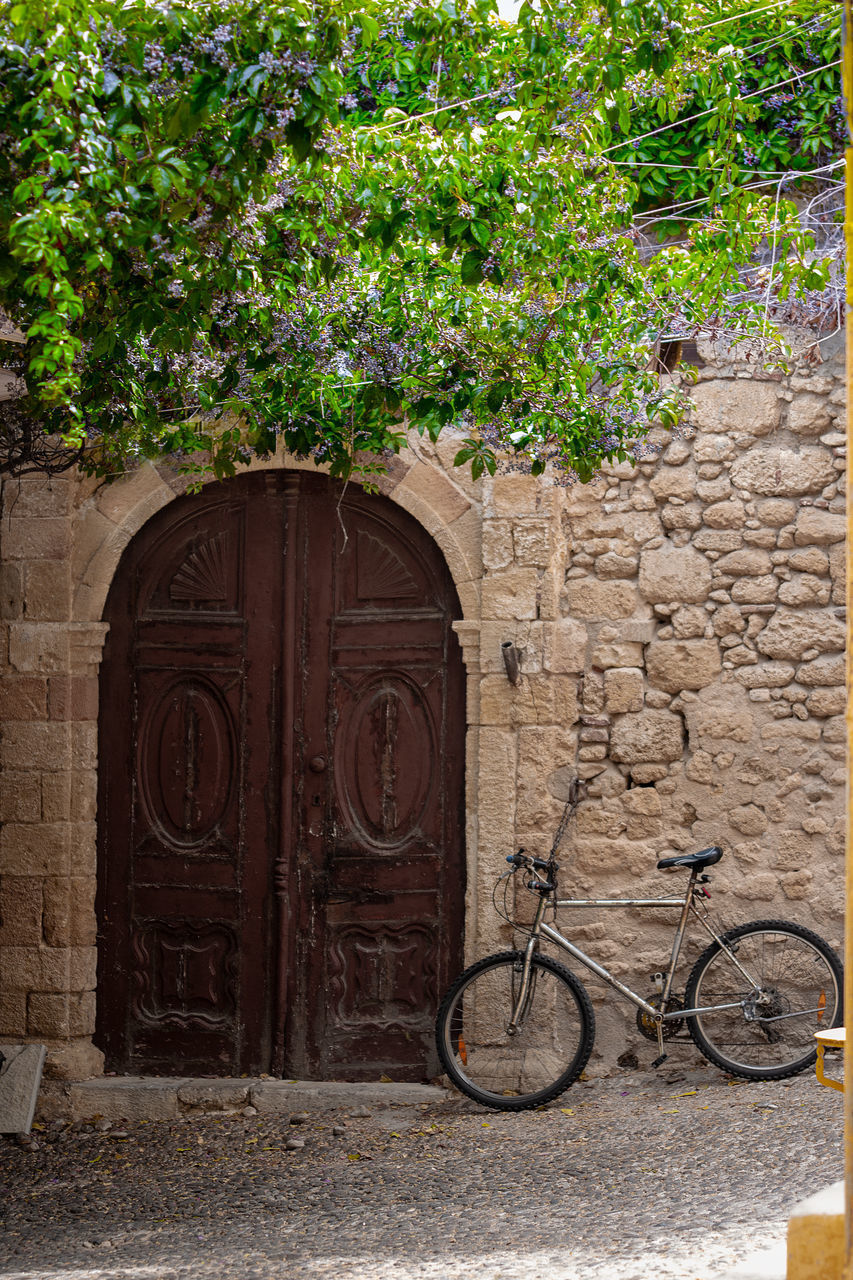 bicycle, plant, architecture, entrance, built structure, no people, building exterior, day, door, wall, growth, nature, wall - building feature, transportation, outdoors, building, stone wall, mode of transportation, stationary, land vehicle