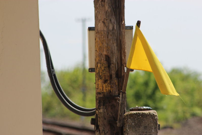 Railway Yellow Flag Control Manage Direct Guide Railwayman Railway Roader Electric Wires Transport Sign Column Pillar Station Wires Danger Day Train Train Station No Train Waiting Flag Rust Old Use No Edit/no Filter EyeEm Selects Yellow Tree Close-up