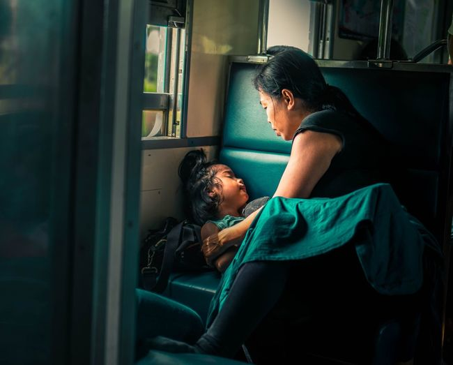 Mother sitting by sleeping daughter in train