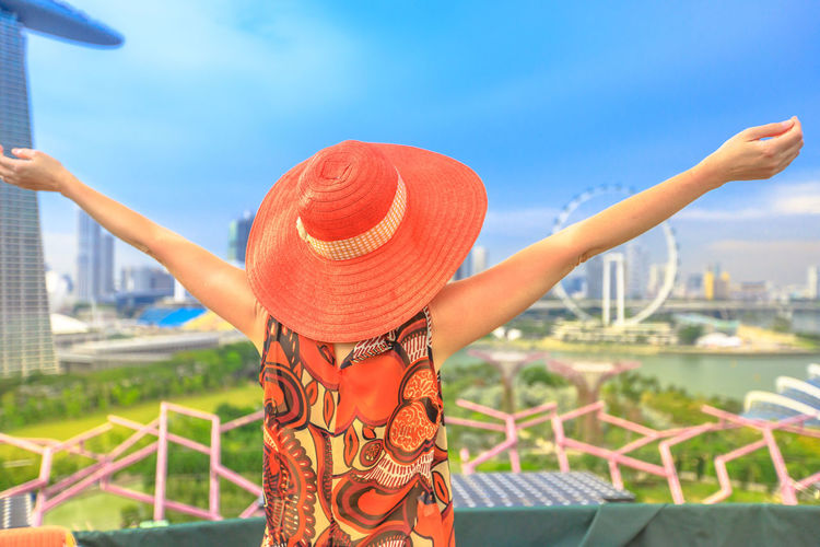 Happy woman in res hat and with open arms enjoying cityscape of Singapore. Blonde tourist above aerial view of Singapore marina. Travel holiday vacation in Singapore, Southeast Asia,Sunny day blue sky Singapore Singapore City Woman Tourist Tourist Attraction  Tourist Destination People Girl Females Aerial View Skyline Cityscape Panorama Happy Travel Hat Lifestyle Enjoy Nature Tourism Smiling Sky Architecture One Person Real People Focus On Foreground Clothing Day Built Structure Lifestyles Women Leisure Activity Human Arm Building Exterior Adult City Outdoors Orange Color Arms Raised Human Limb