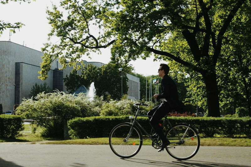 Side view of woman with bicycle against trees