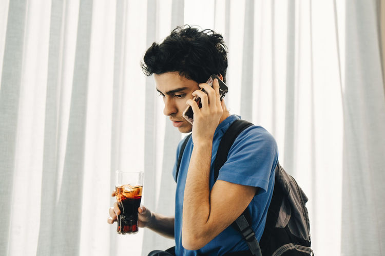 Young man looking away while holding glass window