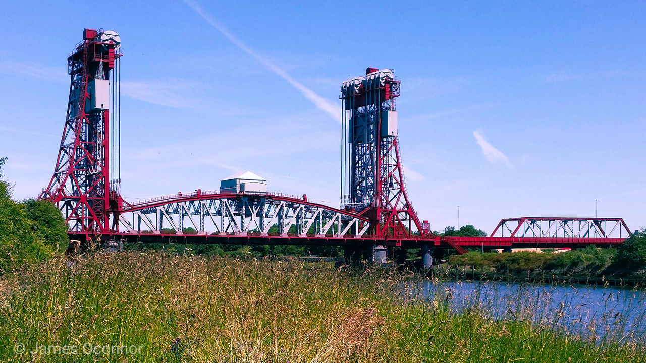 grass, sky, plant, nature, architecture, day, built structure, transportation, outdoors, no people, field, metal, connection, land, bridge, bridge - man made structure, industry, low angle view, red, growth