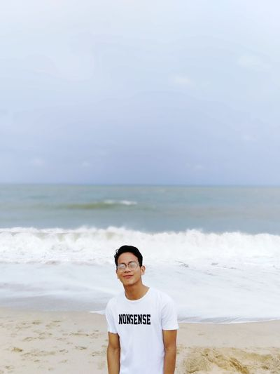 Portrait Of Young Man Standing At Beach Against Sky