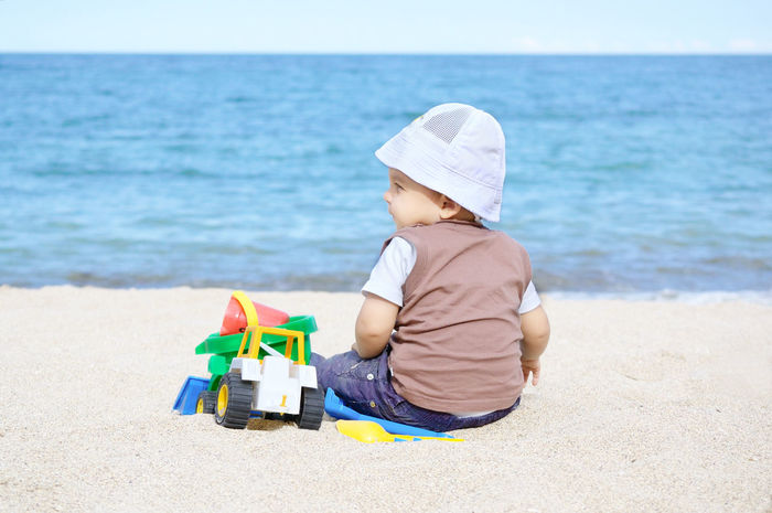 A little baby boy sitting in the sand and playing with his toys on the beach on a summer day Beach Boys Child Childhood Children Only Day Nature One Boy Only One Person Outdoors Playing Sand Sand Pail And Shovel Sea Summer