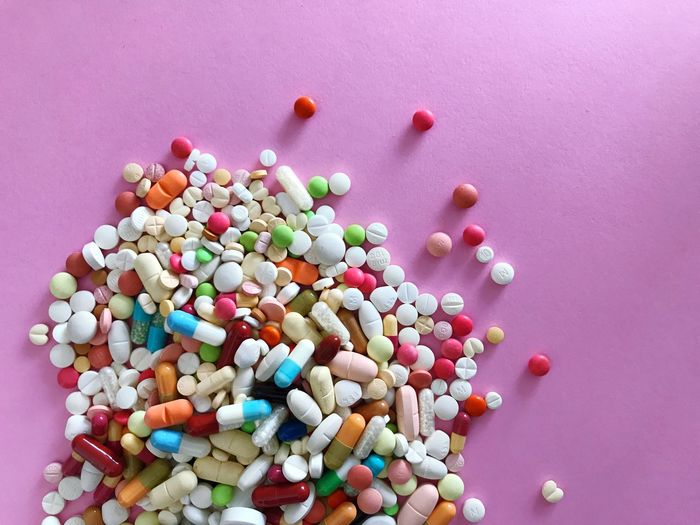 High angle view of colorful medicines on pink background