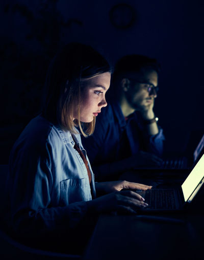 Woman with man using laptop