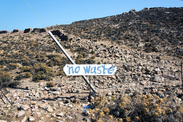 No waste sign on the hills in the island of pATMOS, greece Hiking NO WASTE Nature Sign Signage Clear Sky Communication Day Environment Handwritten Hill Information Information Sign Land Landscape Mountain Nature No People Outdoors Road Rocks Sky Text Waste Western Script