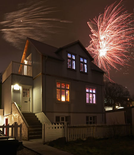 Firework display by building against sky at night
