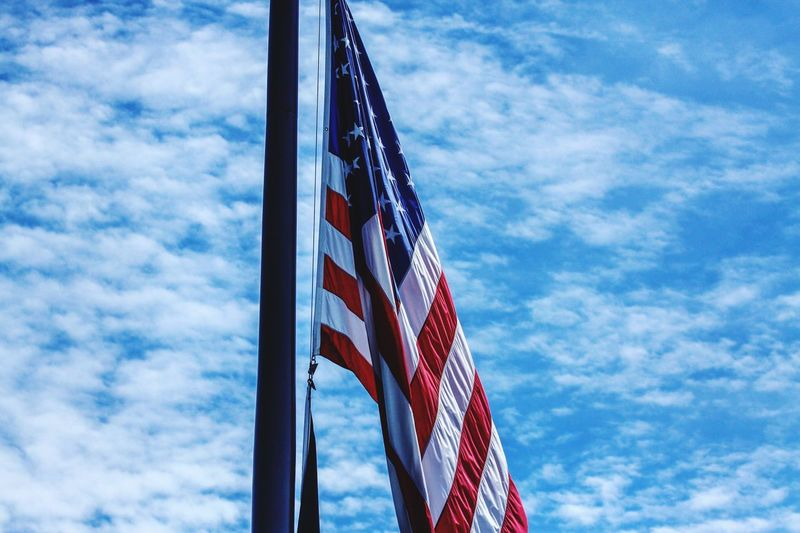 Close-Up Of American Flag Against Clouds