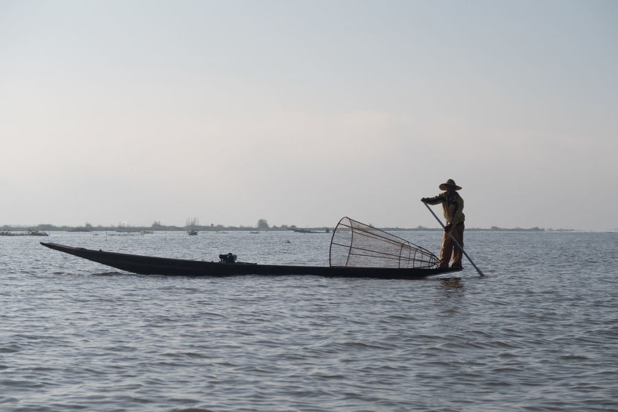 Adults Only Beauty In Nature Burma Day Fisherman Fishing Fishing Boat Fishing Net Fishing Tools Inle Lake Myanmar Nature Nautical Vessel Net Occupation One Person Outdoors People Rowing Sea Silhouette Sky Standing Tradition Water