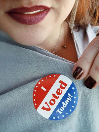 Midsection Of Woman Showing I Voted Today Badge On Top