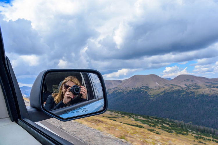 reflection of woman holding digital camera taking picture of rocky mountains from car window Camera Epic Photo Op Reflection Road Taking Photos Beauty In Nature Car Car Interior Cloud - Sky Day Digital Camera Landscape Lifestyles Mountain Nature One Person Outdoors People Real People Road Trip Side-view Mirror Sky Vehicle Interior Window