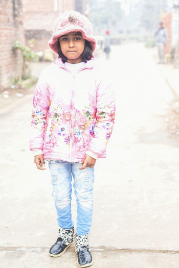 Portrait of smiling girl standing on road